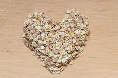 Oat flakes cereal heart shaped on wooden surface. Stock Photo