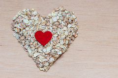Oat flakes cereal heart shaped on wooden surface. Dieting healthcare concept. Oat cereal heart shaped on wooden surface. Healthy food for lowering cholesterol Stock Photos