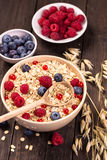 Oat flakes cereal and various berries top view Stock Image
