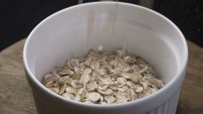 Oat flakes falling into wood olive bowl closeup slow motion footage, prores footage.  stock video