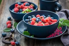 Oat flakes with fresh blueberries and raspberries in blue bowl. On old wooden table Royalty Free Stock Photo