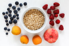 Oat flakes and fruits. On white wooden background Stock Photo