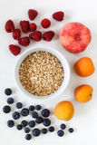 Oat flakes and fruits. On white wooden background Stock Photos