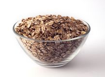 Oat flakes in a glass bowl on white backrgound stock image