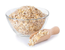 Oat flakes in glass bowl and wooden spoon isolated on white Stock Images