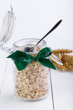 The oat flakes in glass jar and green ribbon. Stock Photos