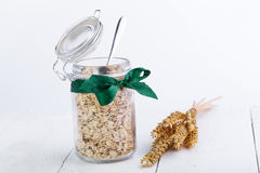 The oat flakes in glass jar and green ribbon. Stock Image