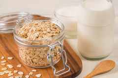 Oat flakes in glass jar and milk bottle Royalty Free Stock Photo