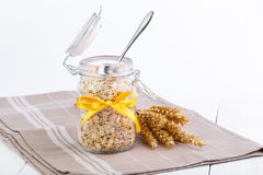 The oat flakes in glass jar with spoon and wheat. Stock Photo