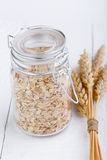 The oat flakes in glass jar and wheat. Royalty Free Stock Photography