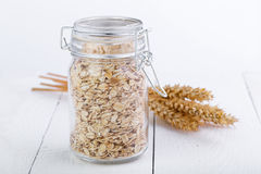 The oat flakes in glass jar and wheat. Stock Photography