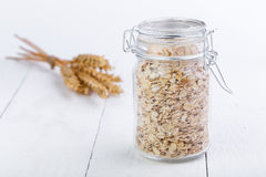 The oat flakes in glass jar and wheat. Royalty Free Stock Images