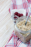 Oat flakes in glass jar on wooden table with raspberry on background Royalty Free Stock Photography