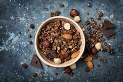 Oat flakes or granola with tasty chocolate and whole nuts for breakfast