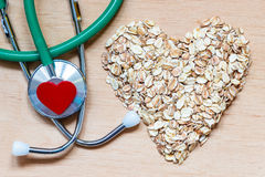 Oat flakes heart shaped and stethoscope. Royalty Free Stock Photos