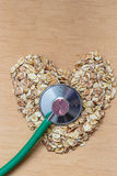 Oat flakes heart shaped and stethoscope. Royalty Free Stock Photography