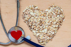 Oat flakes heart shaped and stethoscope. Royalty Free Stock Image