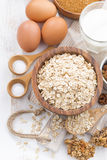 Oat flakes and ingredients on a white wooden table, top view Royalty Free Stock Image