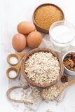 Oat flakes and ingredients on a white wooden table, vertical Stock Image