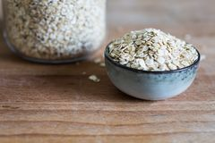 Oat flakes in a jar and piled in a bowl stock photography