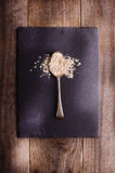 Oat flakes on metal spoon on black stone. Wooden background. Stock Images