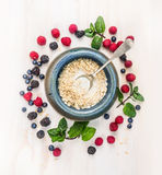 Oat flakes with milk and berries in blue rustic bowl with spoon on white wooden background Royalty Free Stock Images