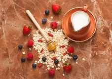 Oat flakes, milk, honey and berries. Food background Stock Images
