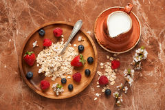 Oat flakes, milk, honey and berries. Stock Photography