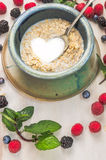 Oat flakes with milk in a shape of heart on summer berries background Royalty Free Stock Photos