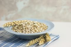 Oat flakes or oatmeal in ceramic bawl on blue table. Prepare oat flakes for bakery or cooking.Natural organic food in vintage styl. E concept.Oat flake, oatmeal stock photo