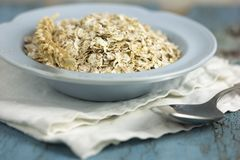 Oat flakes or oatmeal in ceramic bawl on blue table. Prepare oat flakes for bakery or cooking.Natural organic food in vintage styl. E concept.Oat flake, oatmeal royalty free stock photos