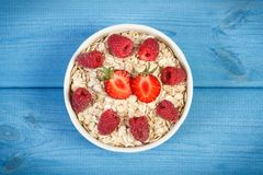 Oat flakes and oatmeal with fruits, healthy lifestyle and nutrition. Fresh prepared oat flakes and oatmeal with fruits, concept of diet, healthy lifestyles and Stock Photos