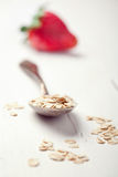 Oat flakes in an old spoon and a strwberry on wooden table, tone Royalty Free Stock Photos