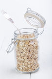The oat flakes in opened glass jar with spoon. Stock Photos