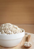 Oat flakes pile in cup. Oat flakes pile in a white cup Stock Photo