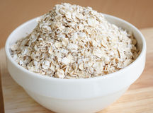 Oat flakes pile in cup. Oat flakes pile in a white cup Royalty Free Stock Image