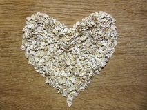 Oat flakes pile in a heart shape on a wooden background royalty free stock image