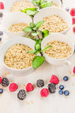 Oat flakes pile  in white bowls with mint and fresh summer berries Stock Photo