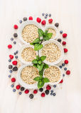 Oat flakes pile in white bowls with peppermint and fresh berries. Top view Stock Image
