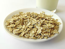 Oat flakes on a plate next to a glass of milk Royalty Free Stock Image