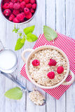Oat flakes. With raspberry in bowl and on a table Stock Photo