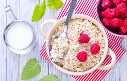 Oat flakes. With raspberry in bowl and on a table Stock Photos