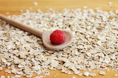 Oat flakes and raspberry in a wooden spoon. Close-up Stock Photography