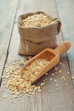 Oat flakes in sac. With wooden scoop on wooden background Stock Photography