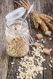 Oat flakes spilled out from jar and wheat. Stock Photography
