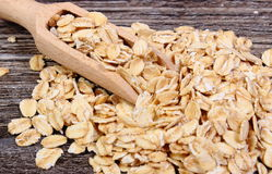 Oat flakes with spoon on wooden background Stock Photos