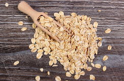 Oat flakes with spoon on wooden background Stock Image