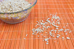 Oat flakes on the table and in a cup. On the table Royalty Free Stock Image