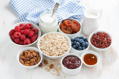 Oat flakes and various delicious ingredients for breakfast. On white wooden table, horizontal Stock Image