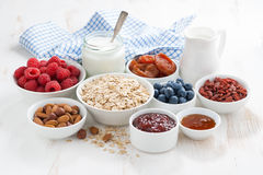 Oat flakes and various ingredients for breakfast on white. Wooden table, horizontal Royalty Free Stock Photography